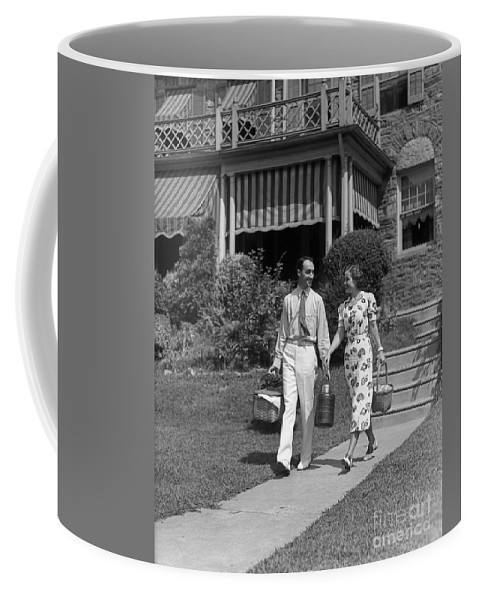 1930s Coffee Mug featuring the photograph Couple Walking Out Of House, C.1930s by H. Armstrong Roberts/ClassicStock