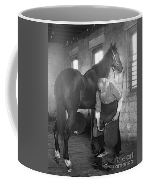1930s Coffee Mug featuring the photograph Elderly Blacksmith Shoeing Horse by H. Armstrong Roberts/ClassicStock