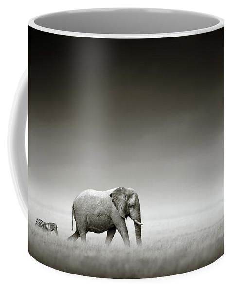 Elephant; Zebra; Behind; Follow; Huge; Big; Grass; Grassland; Field; Open; Plains; Grassfield; Dark; Sky; Together; Togetherness; Art; Artistic; Black; White; B&w; Monochrome; Image; African; Animal; Wildlife; Wild; Mammal; Animal; Two; Moody; Outdoor; Nature; Africa; Nobody; Photograph; Etosha; National; Park; Loxodonta; Africana; Walk; Namibia Coffee Mug featuring the photograph Elephant with zebra by Johan Swanepoel
