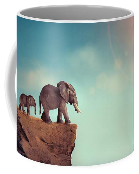 Elephant Coffee Mug featuring the photograph Extinction Concept Elephant Family On Edge Of Cliff by Lee Avison