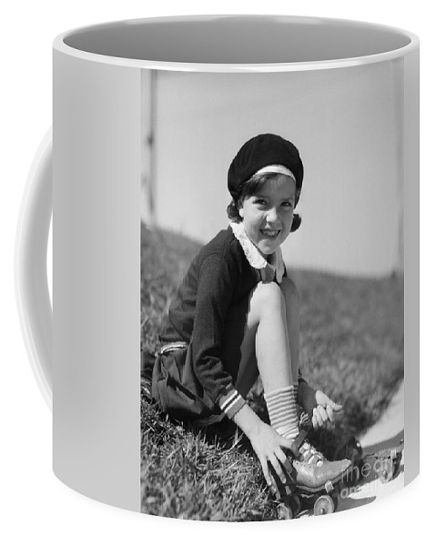 1930s Coffee Mug featuring the photograph Girl Putting On Roller Skates, C.1930s by H. Armstrong Roberts/ClassicStock