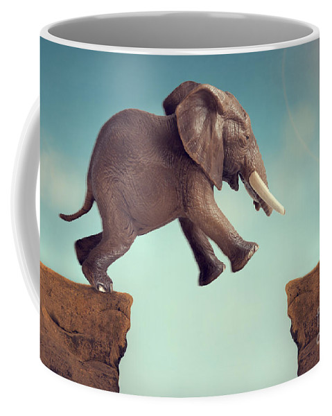 Leap Of Faith Coffee Mug featuring the photograph Leap Of Faith Concept Elephant Jumping Across A Crevasse by Lee Avison