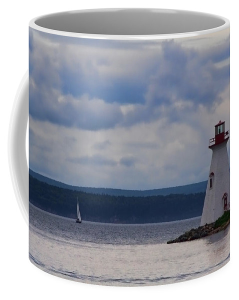 Lighthouse Coffee Mug featuring the photograph Lighthouse And A Sail Boat In Nova Scotia by Sven Brogren