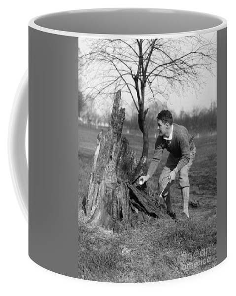 1930s Coffee Mug featuring the photograph Man Retrieving Golf Ball From Tree by H. Armstrong Roberts/ClassicStock
