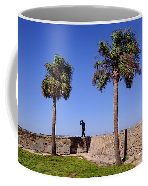 Mclenaghan Coffee Mug featuring the photograph Man With A Hat On The Wall With Palm Trees In Saint Augustine Fl by Travel Back And Forth