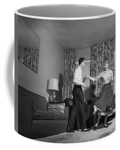 1950s Coffee Mug featuring the photograph Teen Couple Dancing At Home, C.1950s by Debrocke/ClassicStock