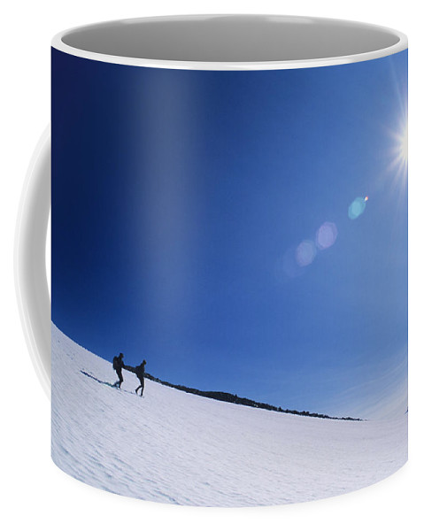 Two People Coffee Mug featuring the photograph Two Hikers Explore A Snowfield by Bill Hatcher