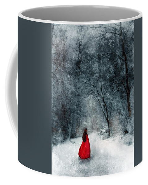 Walking Coffee Mug featuring the photograph Woman In Red Cape Walking In Snowy Woods by Jill Battaglia