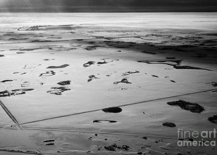 Aerial Greeting Card featuring the photograph aerial view of snow covered prairies and remote isolated farmland in Saskatchewan Canada by Joe Fox