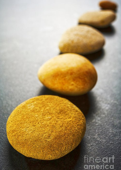 Stone Greeting Card featuring the photograph Diagonal Line Of Brown Pebbles On Dark Background by Colin and Linda McKie