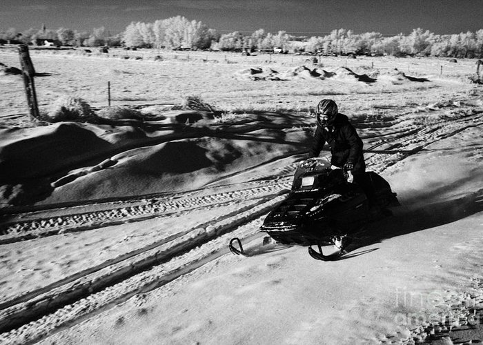 Man Greeting Card featuring the photograph man on snowmobile crossing frozen fields in rural Forget Saskatchewan Canada by Joe Fox