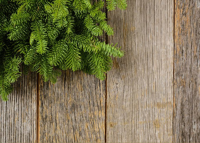 Green Greeting Card featuring the photograph Tree Branch On Rustic Wooden Background Used For Christmas Decor by Brandon Bourdages