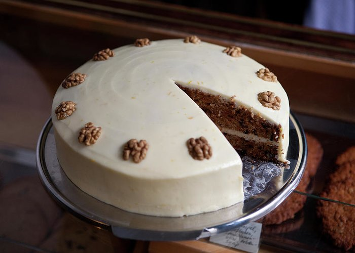 Unhealthy Eating Greeting Card featuring the photograph A Carrot Cake On A Display Cabinet In A by Halfdark