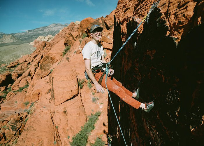 Day Greeting Card featuring the photograph A Climber On Panty Wall In Red Rock by Ryan Tuttle