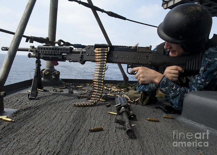 Military Greeting Card featuring the photograph A Sailor Fires An M-240b Machine Gun by Stocktrek Images