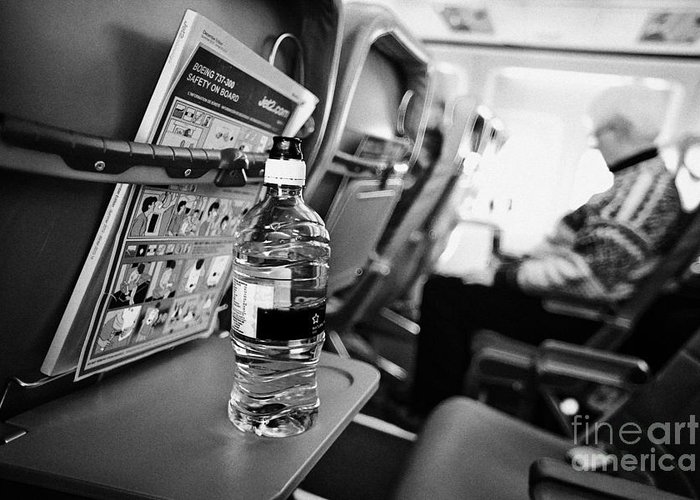 Interior Greeting Card featuring the photograph Bottle Of Water On Tray Table Interior Of Jet2 Aircraft Passenger Cabin In Flight by Joe Fox