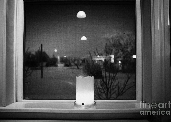 Looking Greeting Card featuring the photograph candle in the window looking out over snow covered scene in small rural village of Forget Saskatchew by Joe Fox