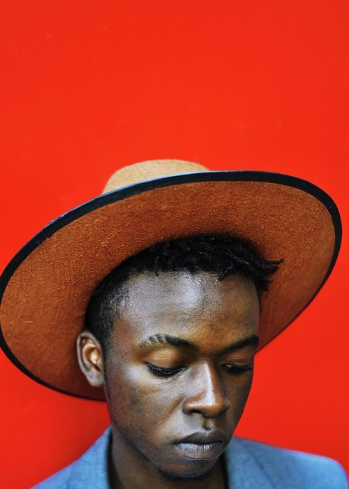 Young Men Greeting Card featuring the photograph Close-up Of Man Wearing Hat Against Red by Samson Wamalwa / Eyeem