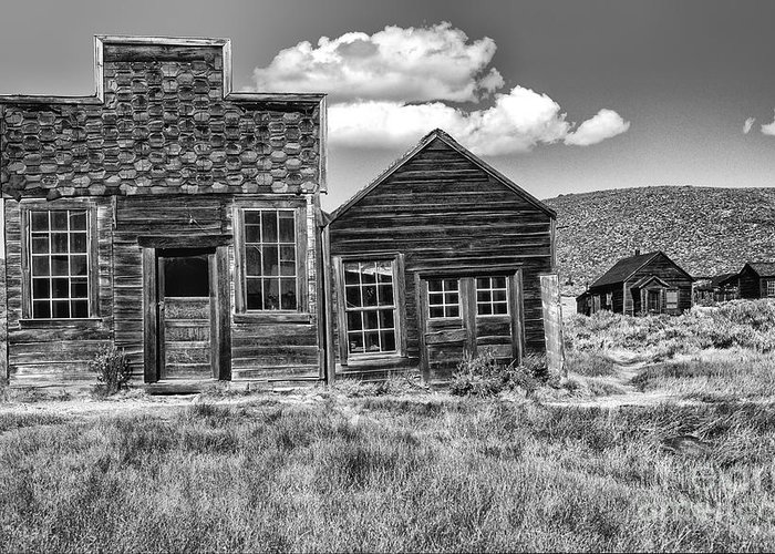 Black & White;black + White;monochrome;black And White;architecture;detail;details;cabins;structures;wood;windows;doors;door;window;buildings;dilapidated;rundown;abandoned;forlorn;derelict;empty;sandra Bronstein;clouds;doorways;entrances;old West;out West;bodie;ghost Town;ghost Towns;california;gold Rush Days;mining;houses;house;residence;horizontal;fine Art Photography;iconic;travel;tourism;historical;state Park;popular;dated;unoccupied;panes;glass;western United States;canvas; Greeting Card featuring the photograph Days Of Glory Gone by Sandra Bronstein