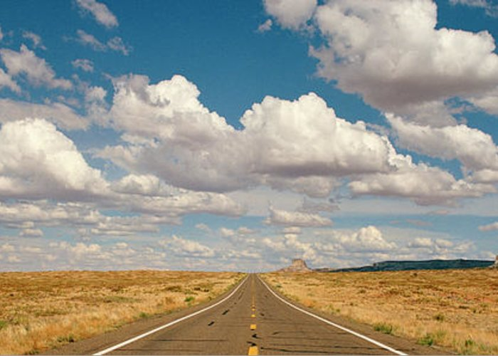 Scenics Greeting Card featuring the photograph Desert Road With Cloud Formations Above by Gary Yeowell