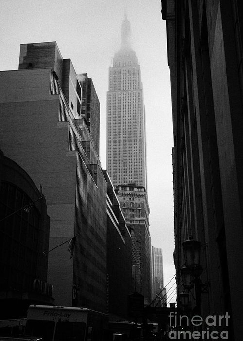 Usa Greeting Card featuring the photograph empire state building shrouded in mist in amongst dark cold buildings on 33rd Street new york city by Joe Fox