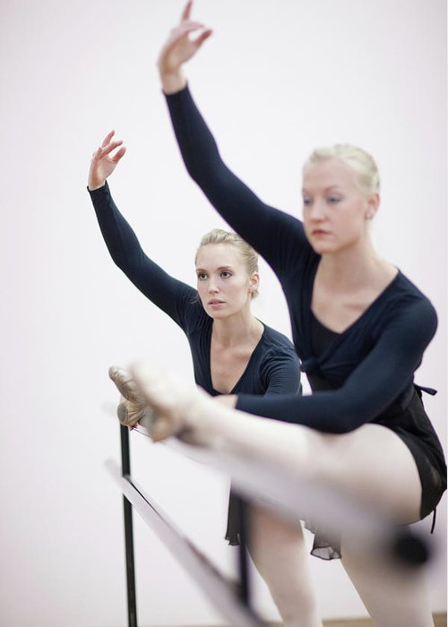 Ballet Dancer Greeting Card featuring the photograph Female Ballerinas Stretching At The by Zero Creatives