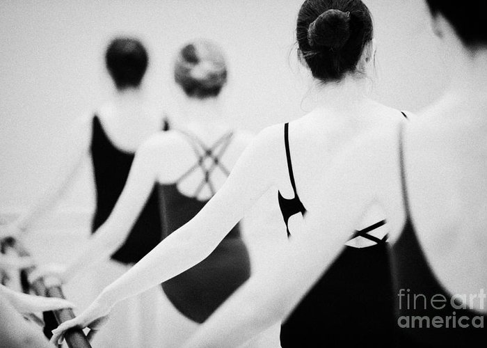Ballet Greeting Card featuring the photograph Female Teenage Ballet Students Holding On To A Ballet Barre At A Ballet School In The Uk by Joe Fox