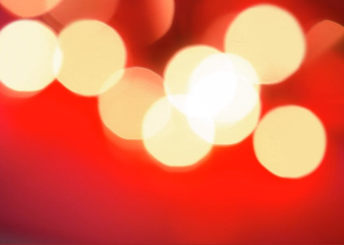 Christmas Lights Greeting Card featuring the photograph Glowing Light On Red Background, Studio by Tetra Images