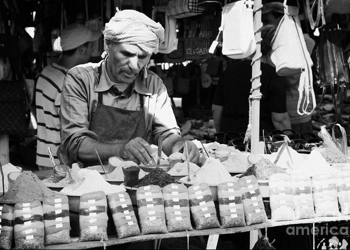 Tunisia Greeting Card featuring the photograph Local Arab Man Measuring Out A Quantity Of Spice For Sale On Stall Of Spices At The Market In Nabeul Tunisia by Joe Fox