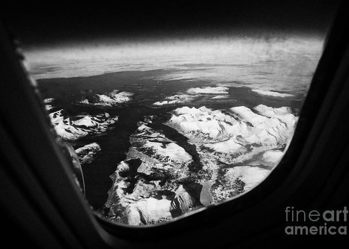 Looking Greeting Card featuring the photograph Looking Out Of Aircraft Window Over Snow Covered Fjords And Coastline Of Norway by Joe Fox