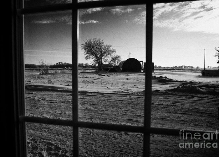 Looking Greeting Card featuring the photograph looking out through door window to snow covered scene in small rural village of Forget Saskatchewan by Joe Fox