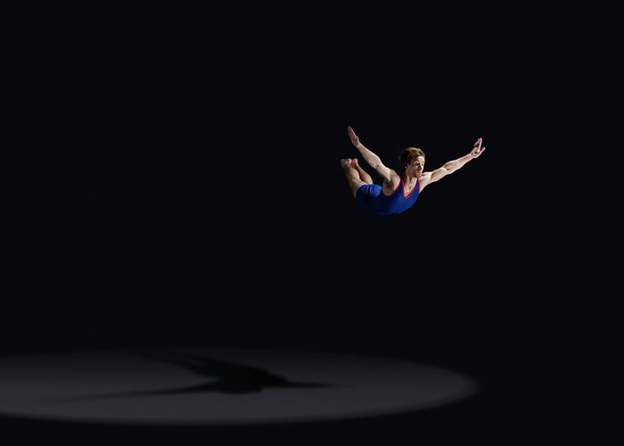Expertise Greeting Card featuring the photograph Male Gymnast Soaring Through The Air by Mike Harrington