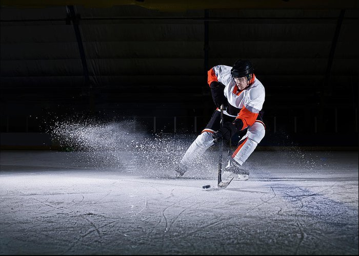 Focus Greeting Card featuring the photograph Male Ice Hockey Player Taking Puck by Mike Harrington