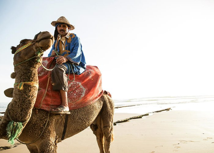Agadir Greeting Card featuring the photograph Man On Camel On Beach, Taghazout by Tim E White
