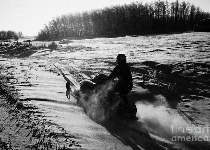 Man Greeting Card featuring the photograph man on snowmobile crossing frozen fields in rural Forget canada by Joe Fox
