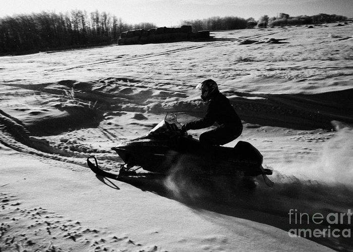 Man Greeting Card featuring the photograph man on snowmobile crossing frozen fields in rural Forget Saskatchewan by Joe Fox