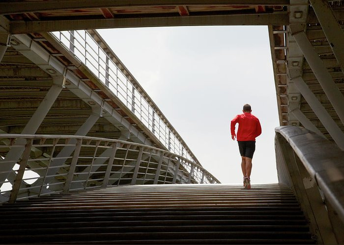 Steps Greeting Card featuring the photograph Man Running Up A Bridge by Chris Tobin