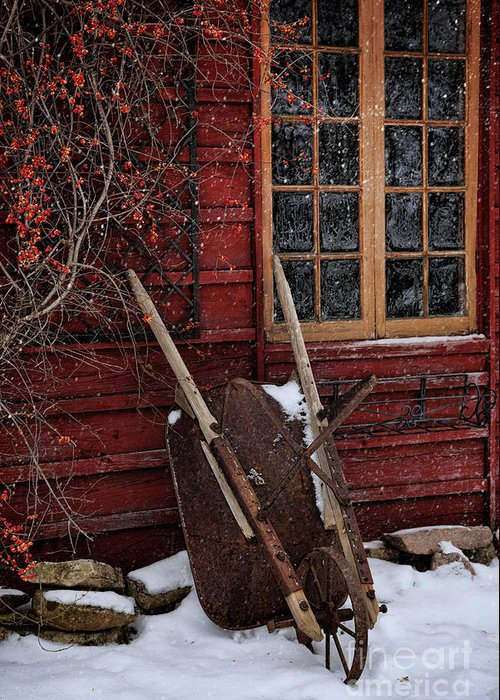 Atmosphere Greeting Card featuring the photograph Old Wheelbarrow Leaning Against Barn In Winter by Sandra Cunningham
