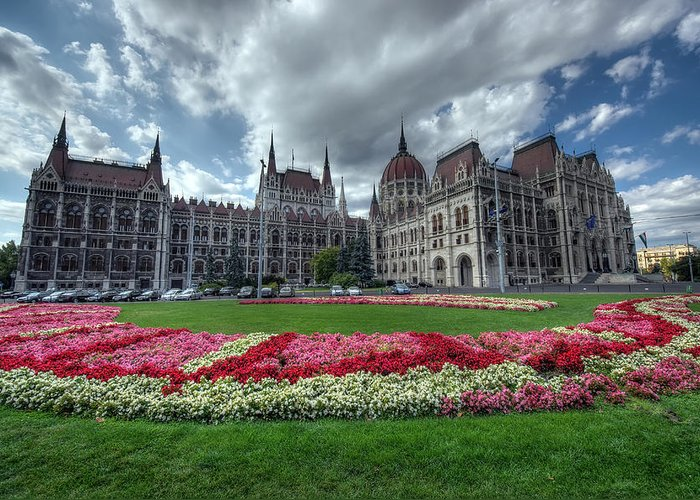 Architecture; Bank; Budapest; Building; Capital; City; Cityscape; Courtyard; Cupola; Day; Destination; East; Europa; Europe; Flowers; Grass; Green; Hungary; Landmark; Meadow; Metropolis; Old; Park; Parliament; Plants; Sightseeing; Tourism; Town; Travel; Urban; Yard; Garden; Wide; Dark; Greeting Card featuring the photograph Parliament Garden Budapest by Ioan Panaite