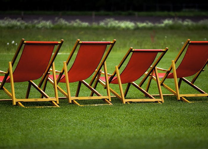 Lounge Greeting Card featuring the photograph Red Deck Chairs On The Green Lawn by Mikhail Pankov