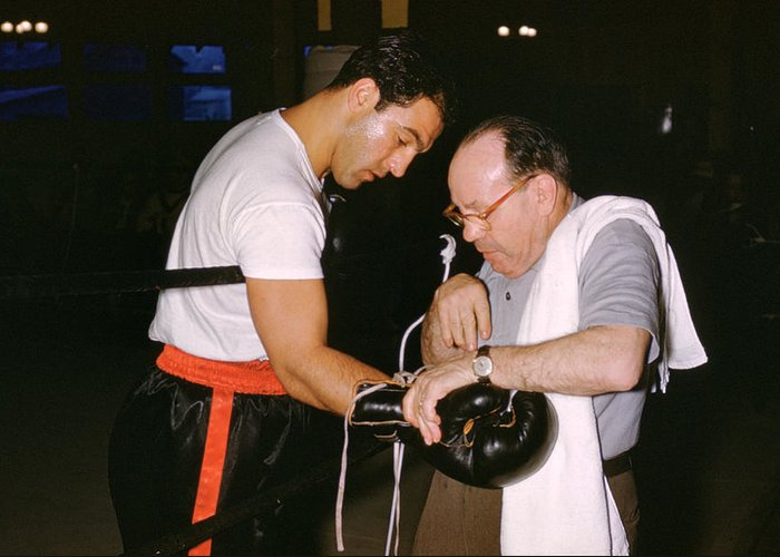 Marvin Newman Greeting Card featuring the photograph Rocky Marciano Looking At Glove by Retro Images Archive