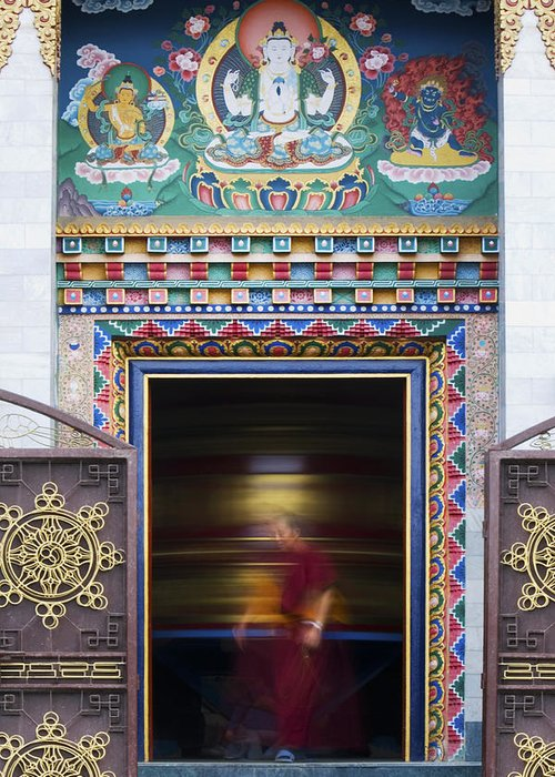 Buddha Greeting Card featuring the photograph Tibetan Monk And The Prayer Wheel by Tim Gainey