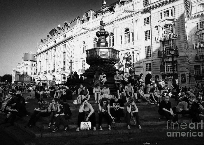 Tourists Greeting Card featuring the photograph tourists and visitors sit on the steps of the eros statue in picadilly circus London England UK by Joe Fox
