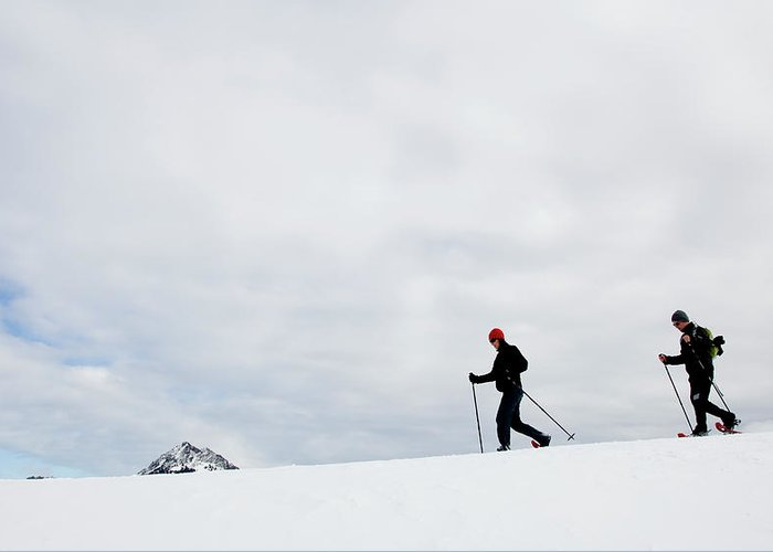 Active Greeting Card featuring the photograph Two People Snow Shoeing Along A Ridge by Jordan Siemens