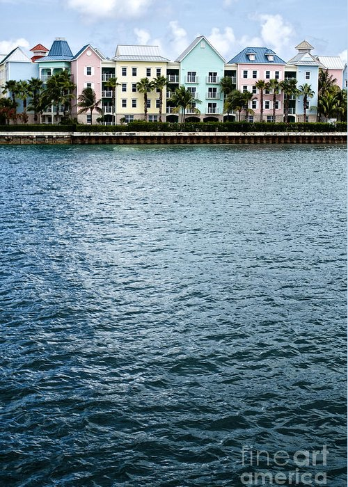 House; Condo; Townhome; Water; Shallow; Island; Tropical; Shore; Waterfront; Bahamas; Blue; Sky; Clouds; Trees; Buildings; Colors; Colorful; Pink; Yellow; Green; Festive; Palm Trees; Outside; Outdoors; Exterior; Home; Tropics; Row Greeting Card featuring the photograph Waterfront Colors by Margie Hurwich