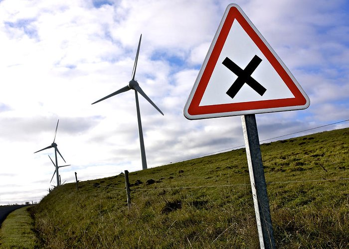 Wind Turbine Greeting Card featuring the photograph Wind Turbines On The Edge Of A Field With A Road Sign In Foreground. by Bernard Jaubert