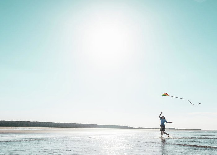 Three Quarter Length Greeting Card featuring the photograph Woman Flying Kite On Beach by Dan Brownsword