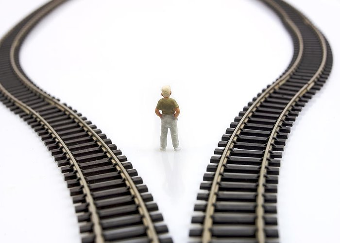 Decides Greeting Card featuring the photograph Figurine Between Two Tracks Leading Into Different Directions Symbolic Image For Making Decisions. by Bernard Jaubert