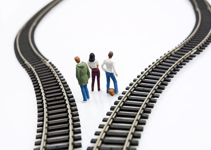 Reflective Greeting Card featuring the photograph Figurines Between Two Tracks Leading Into Different Directions Symbolic Image For Making Decisions. by Bernard Jaubert