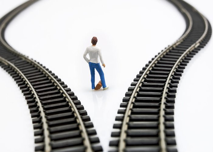 Ponder Greeting Card featuring the photograph Figurine Between Two Tracks Leading Into Different Directions Symbolic Image For Making Decisions. by Bernard Jaubert